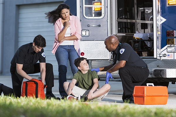 Multi-ethnic paramedics helping boy (12 years) outside ambulance while mother (30s) watches.