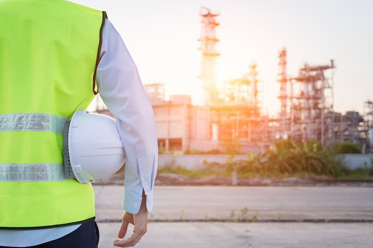 Engineering man standing with white safety helmet near to oil refinery