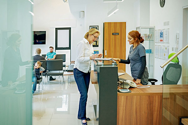 Mature woman standing at the reception desk in a dental clinic filling out the papers
