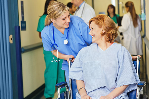 Friendly emergency room nurse assisting wheelchair patient in hospital