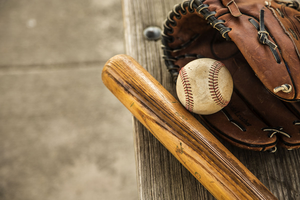 Spring and summer baseball season is here.  Wooden bat, glove, and weathered ball lying on dugout bench in late afternoon sun.  No people.  Great background image.