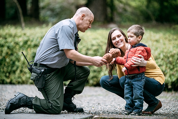 An on duty law enforcement officer talks to a young toddler boy and his mother, giving the child a stuffed a bear.