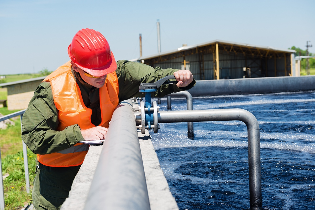 An engineer controlling the quality of water , aerated activated sludge tank at a waste water treatment plant .Copy space